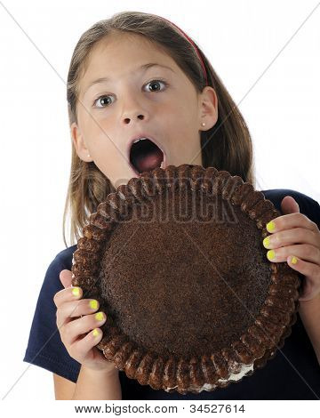 An attractive elementary girl, happily surprised by the giant-sized cookie she's holding.  Room on the cookie for your text.  On a white background.