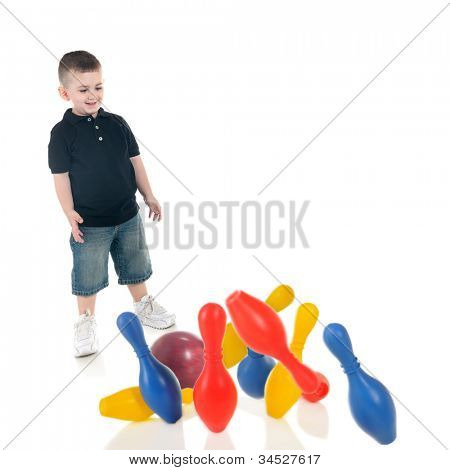 An adorable preschooler happy with the strike ge got when he rolled a standard bowling ball into his toy plastic pins.  Focus on child, motion blur on ball and pins.  On a white background.