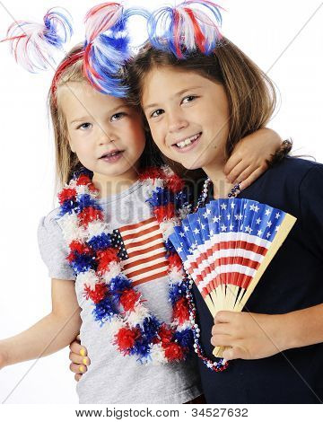 Two close young sisters celebrating America's Independence together.  Both are dressed with red, white and blue accessories.  On a white background.