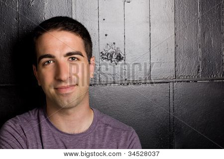 Cute Young Man Leaning On Black Wall