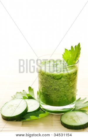 Glass of healthy green cucumber smoothie decorated with celery leaves