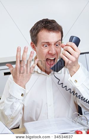 Angry business man yelling at phone in the office