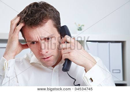 Frustrated business man waiting on the phone in a hotline queue