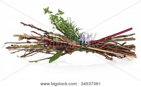 Witches bundle of herbs, twigs and rosemary herb flowers tied in a bundle on white background.