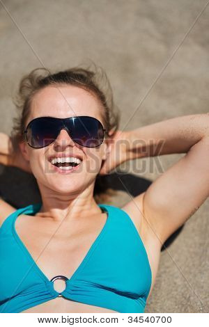 Portrait Of Smiling Woman Laying On Sand Beach