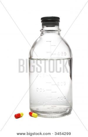 Medical Bottle With Saline And Pills Beside It
