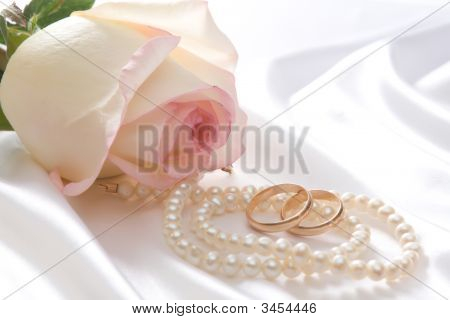 Rose, Pearls And Wedrings Over White Satin