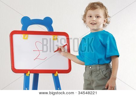 Little smiling boy drew a pound sign on the whiteboard