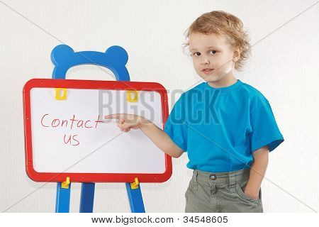 Little cute smiling boy shows the word contact us on a whiteboard