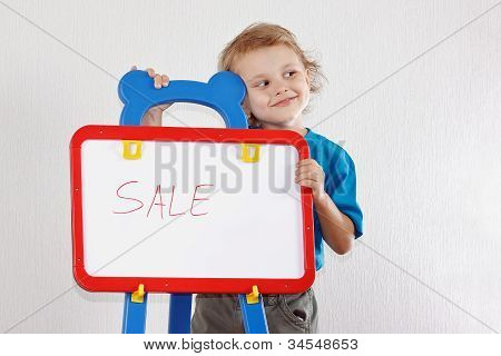Little cute smiling boy shows the word sale on a whiteboard