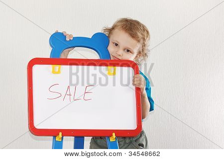 Little cute boy shows the word sale on a whiteboard