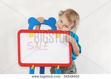 Little smiling boy shows the word sale on a whiteboard