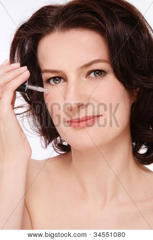 Portrait of attractive groomed healthy middle-aged woman applying serum on her face
