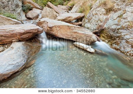 Small waterfall casdcading over rocks in blue pond