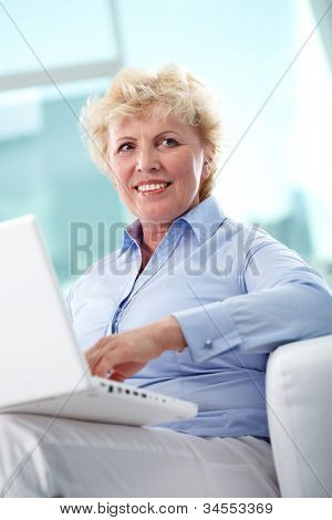 Portrait of friendly aged woman typing and smiling