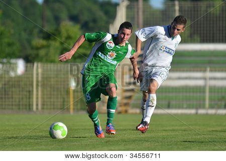 KAPOSVAR, HUNGARY - JUNE 16: Krisztian Garai (in white) in action at the Hungarian National Championship under 19 game Kaposvar (white) vs. Paks (green) on June 16, 2012 in Kaposvar, Hungary.