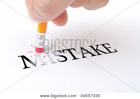 """Male hand holding wooden pencil and delete word """"MISTAKE"""" on the white paper"""