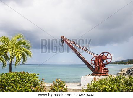 Old Red Rusty Crane By Palm Tree