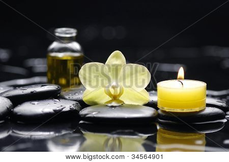 Yellow candle with bottle of essential oil and orchid on pebble