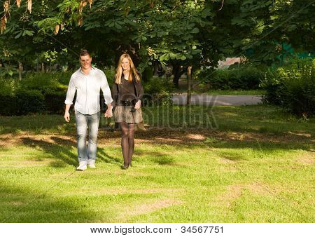 Young Couple Holding Hands In The Park.