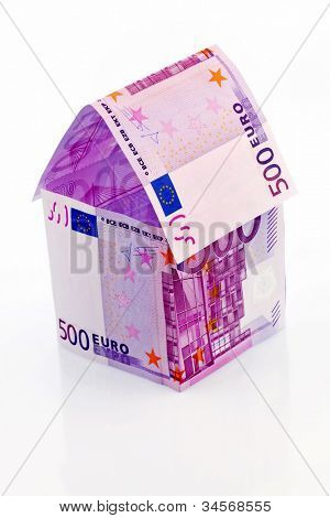 a house built with money seem �?�¢�¢�?�?�?�¬ on a white background. savings, house building and home buying.