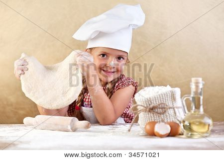 Little girl making pizza or pasta dough smeary with flour