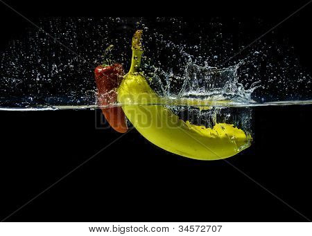 Red fresno pepper and yellow banana splashing in water