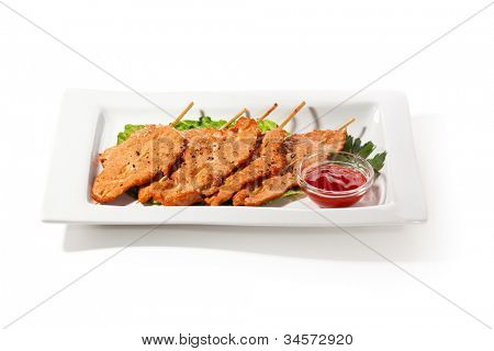Chinese Cuisine - Skewered Pork on Salad Leaf with Spicy Sauce