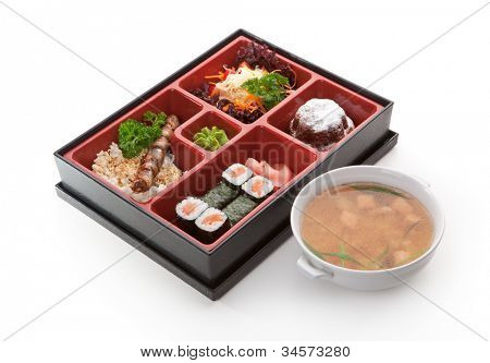 Japanese Meal in a Box (Bento) - Salad, Skewered Meat with Rice, Salmon Sushi Roll and Dessert. Garnished with Miso Soup