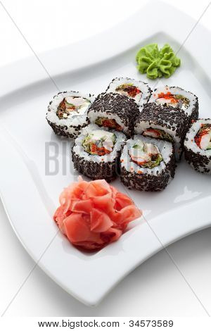 Japanese Cuisine - Sushi Roll with Shrimps, Eel, Salad Leaf, Cream Cheese and Tobiko inside. Sesame outside