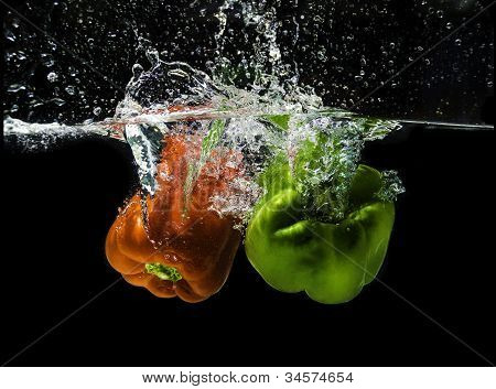 Sweet red and green peppers, splashing in clear water
