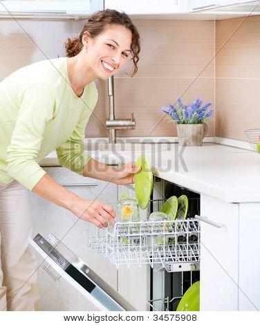 Lavavajillas. Mujer joven en la cocina haciendo las tareas domésticas. Lave-para arriba