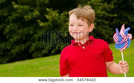 Child playing with American flag pinwheel to celebrate Independence Day on July Fourth
