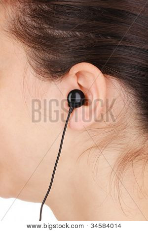 Human ear with earphone close-up