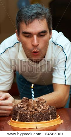 man blowing out birthday candle