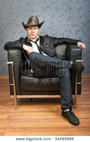 Young Cowboy Sitting In Leather Chair In The Interior