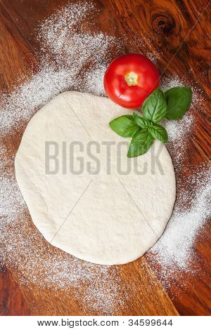 Pizza dough, tomato and basil on wooden table