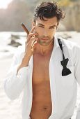 picture of bare chested  - Great looking sexy male model with open white shirt and loose bow tie smoking cigar on beach - JPG