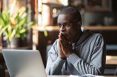 Hopeful Black Guy Hope For Best Reading News On Laptop poster
