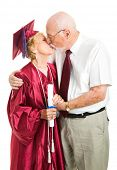 Senior woman gets a kiss from her husband on her graduation day.  Isolated on white.