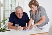 stock photo of scrabble  - Portrait of mature couple playing scrabble game - JPG