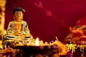Front View Of Golden Statue Of Buddha With Shining Diya Against Blurry Red Bacground. Faith And Budd poster