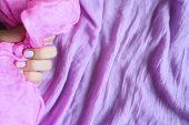 A Woman Hand With Pale Lilac Nails Holds A Pink Silk Fabric Against A Background Of Lilac Cotton Fab poster