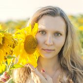 Young Girl Holding Sunflowers Outdoor Shot. Portrait Of Beautiful Blonde Girl With Bright Yellow Sun poster