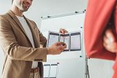 Cropped View Of Smiling Designer Presenting Wireframe Sketches For Mobile Website To Colleague In De poster