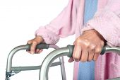 An elderly senior adult using a walker to help her mobility.  Focus is on the hand.