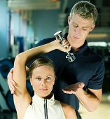 pic of personal trainer  - Young woman lifting a dumb - JPG