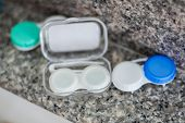 Accessories For Working With Contact Lenses. Tweezers With Contact Lens And Plastic Container On Gra poster