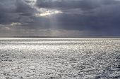 Dramatic Illuminated Coastal Scenery Near Neuharlingersiel In Eastern Frisia, Germany poster