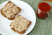 picture of chipotle  - Open faced chipotle salmon organic mayonnaise spread on two slices of toasted complete protein sesame sprouted grain bread with a glass mug of tomato vegetable juice - JPG